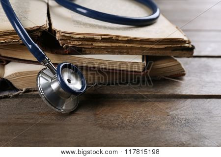 Book and stethoscope on wooden table closeup