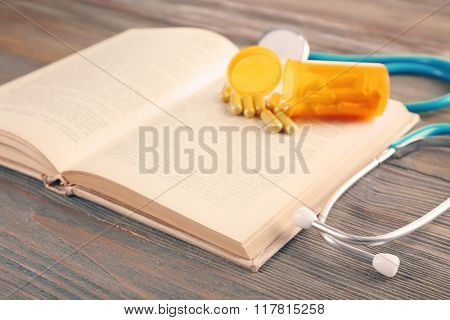 Book, pills and stethoscope on wooden table closeup
