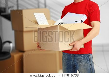 Man holding carton box full of office stationery in the room, close up