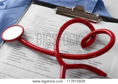 Stethoscope and patient card, close-up