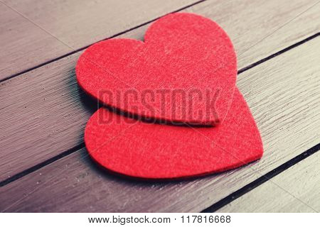 Red felt hearts on purple wooden background