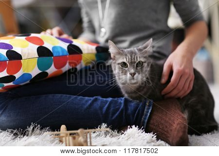 Woman sitting with cat on fur carpet at home