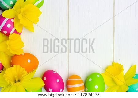 Easter eggs and daffodils corner border over white wood