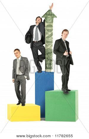 Three Businesmen On Wood Toy Blocks Victory Podium With Dollar Arrow Collage