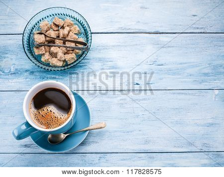 Cup of coffee and cane sugar cubes on old blue wooden table.