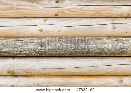 Closeup background texture of a wall made of bright wooden logs