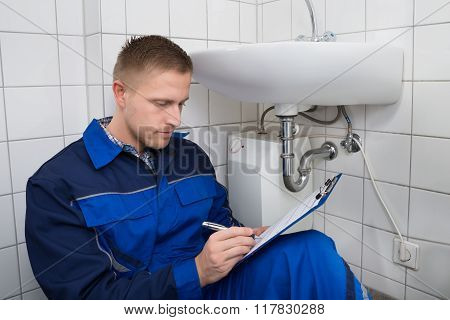 Young Plumber Writing On Clipboard