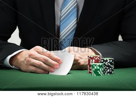 Poker Player Hand With Cards And Chips