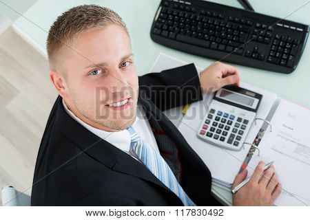 Happy Businessman Calculating Invoice