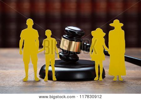 Paper Family With Mallet On Table In Courtroom
