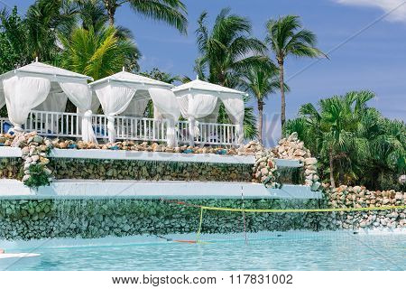 gorgeous splendid view of beautiful swimming pool in tropical garden with white fluffy inviting gaze