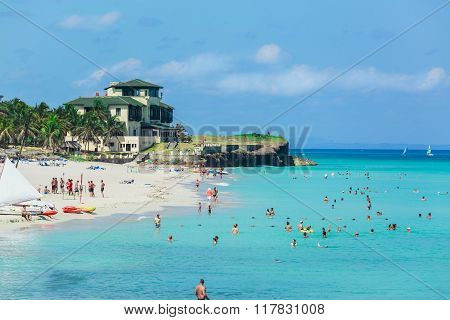 nice gorgeous beach with people relaxing and swimming in turquoise ocean