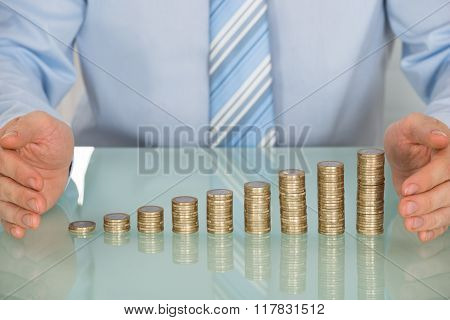 Businessman Protecting Stack Of Coins