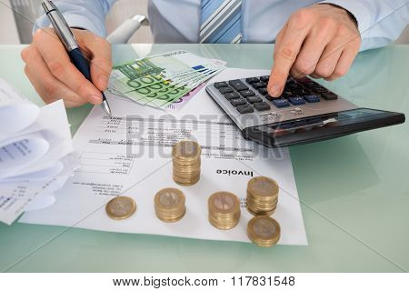 Businessman Calculating Invoice With Money At Desk