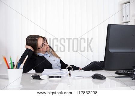 Tired Businesswoman Leaning On Desk