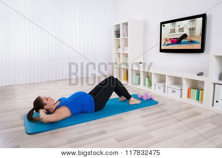 Pregnant Female Doing Workout By Lying On Exercise Mat