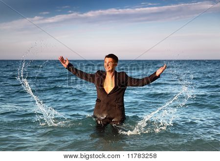 Smiling Man In Suit Stands In Sea And Splash Water At Evening