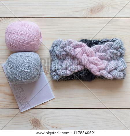 two skeins of wool and knitted headband gradient on the wooden background