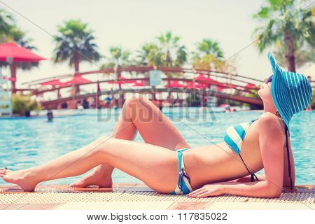 Beautiful woman on summer holidays at the swimming pool