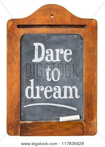 Dare to dream blackboard sign  - white chalk text  on a small slate message blackboard isolated on white