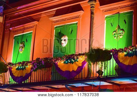 February 2, 2016 in New Orleans, LA:  Mardi Gras decorations on the residential balcony with wooden shutters taken at the French Quarter where tourists and locals celebrate Mardi Gras in New Orleans, LA
