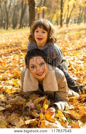 Son On Top Her Mother In Autumn Park