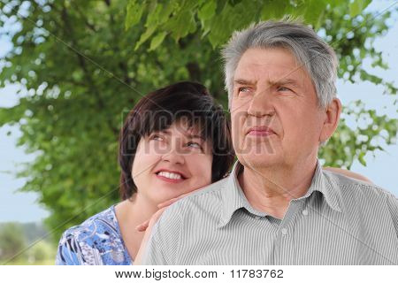 Portrait Of Old Senior, His Adult Daughter Leans On His Shoulder And Smiling, Summer Trees And Sky