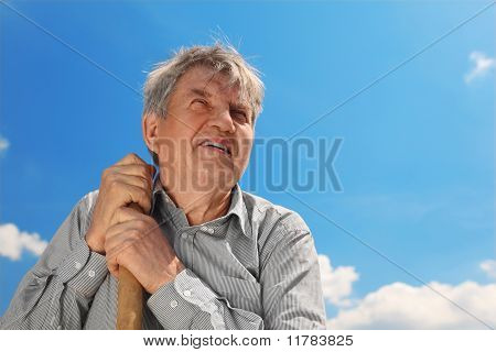 Old Senior In Striped Shirt With Shove Smiling And Looking At Side, Blue Sky With Clouds