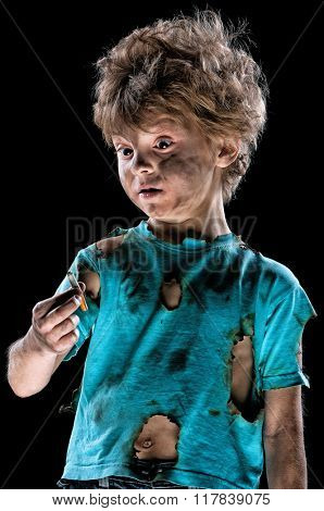 Portrait of burnt little boy with cigarette butt, over black background