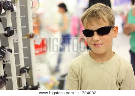 Portrait Of Little Boy Trying Black Sunglasses In Store