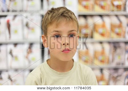 Portrait Of Little Caucasian Boy Looking At Side, Counter In Store With Commodity