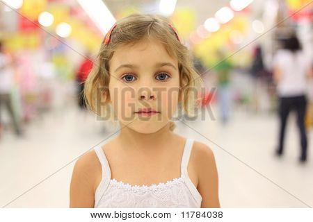 Portrait Of Little Serious Girl Standing In Big Store Alone And Looking At Camera