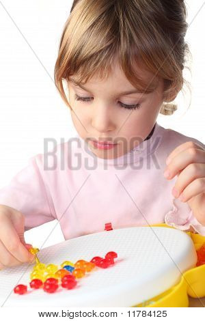 Little Girl In Pink Shirt Playing With Colorful Plastic Mosaic And Looking On It