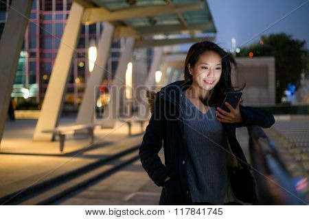 Woman read on text message on phone at night