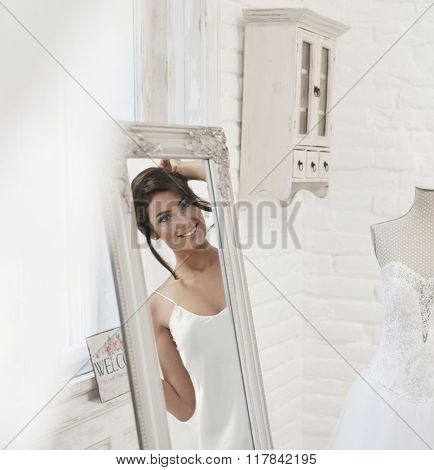 Beautiful young bride looking at herself in mirror on wedding-day, smiling happy.