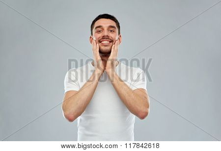 beauty, skin care, grooming and people concept - happy young man touching his face applying aftershave over gray background