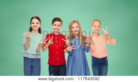 childhood, education, friendship and people concept - happy smiling boy and girls showing peace hand sign over green school chalk board background
