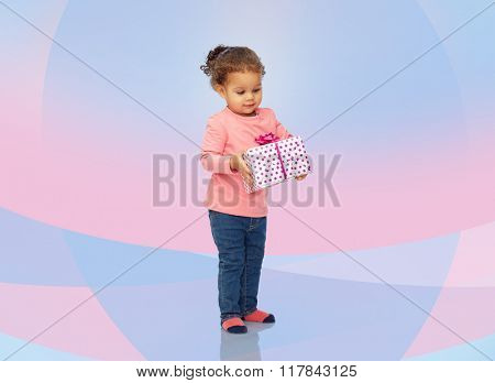 childhood, fashion, birthday, holidays and people concept - beautiful little african american baby girl with gift box over pink violet background