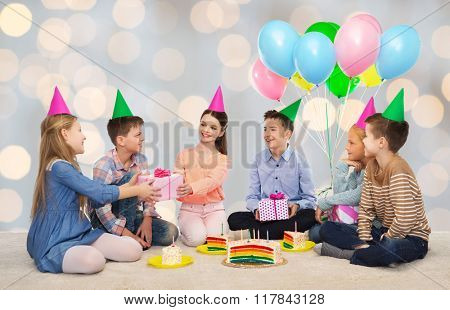 childhood, holidays, celebration, friendship and people concept - happy smiling children in party hats with cake giving presents at birthday party over lights background