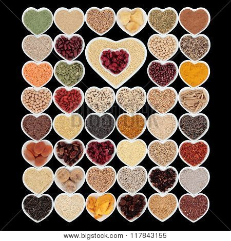 Large dried superfood collection in heart shaped porcelain china bowls forming an abstract background  over black background. High in minerals, vitamins and antioxidants.