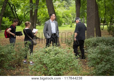 RUSSIA, MOSCOW - 30 JUL, 2015: Actor Alexander Nevsky with assistant are standing in the Sokolniki park at shooting movie (Maximum shock).