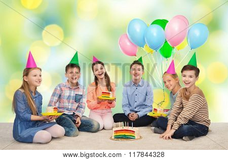 childhood, holidays, celebration, friendship and people concept - happy smiling children in party hats with birthday cake and balloons over green summer holidays lights background