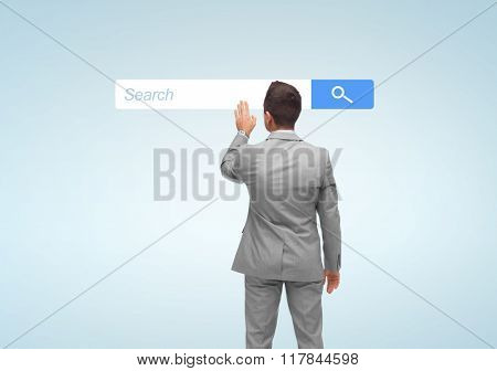 business, people, internet and technology concept - businessman touching virtual projection of browser search bar from back