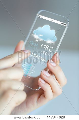 business, technology, forecast and people concept - close up of woman hand holding and showing transparent smartphone with weather cast on screen