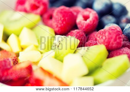healthy eating, dieting, vegetarian food and people concept - close up of fruits and berries in bowl