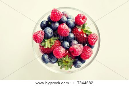 healthy eating, dieting, vegetarian food and people concept - close up of summer berries in glass bowl