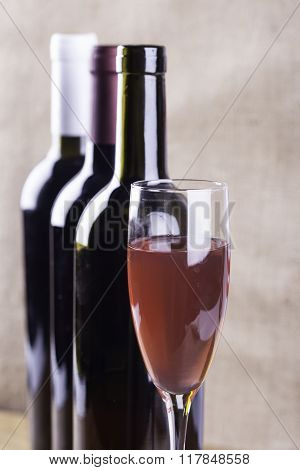 glass of rose wine on the background bottles