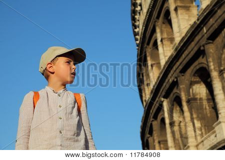 Little Boy In Cap And Backpack Looks At Old, Stone Walls Of The Coliseum