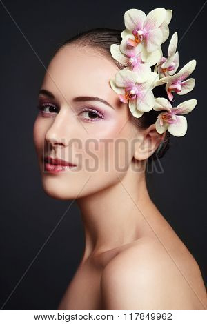 Portrait of young beautiful woman with fresh make-up and white orchid