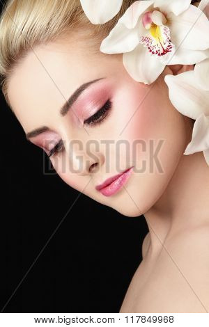 Close-up portrait of young beautiful healthy woman with fresh make-up and white orchid